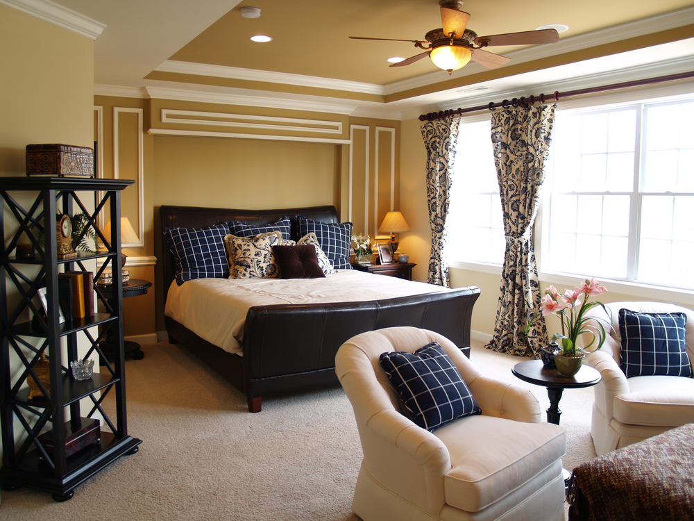 Nicely decorated master bedroom in a newly built luxury home. There is a black leather sleigh bed, dark furniture, light streaming through the windows, and a light sitting area.